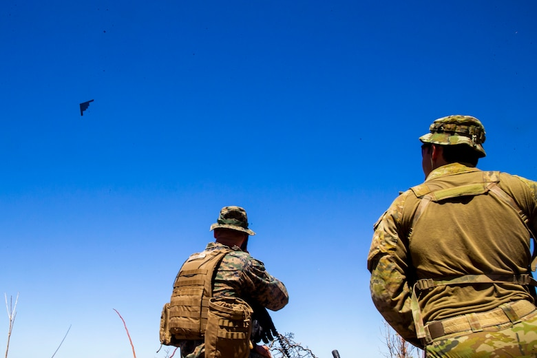 U.S. Marine Corps Capt. Benjamin Hovies with Command Element, Marine Rotational Force – Darwin, and Australian Army Sgt. Aaron Costas direct the flight path of a U.S. Air Force B-2 Spirit Bomber at Mount Bundey Training Area, Northern Territory, Australia, Aug. 24, 2020. Hovies is a native of Lebanon, Tenn. and Costas is a native of Imbil, Queensland. Within the training scenario, a combined team of U.S. Marines and Australian Defence Forces provided target information to U.S. Air Force bombers conducting deep strikes on notional targets. (U.S. Marine Corps photo by Cpl. Harrison Rakhshani)