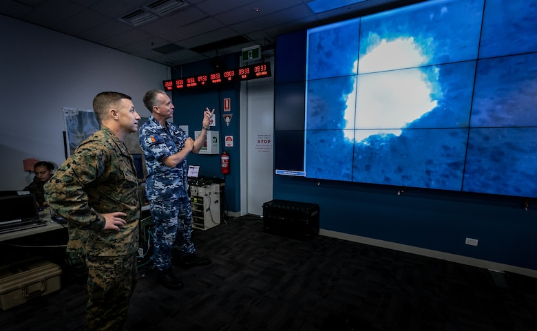 U.S. Marine Corps Col. David M. Banning and Royal Australian Air Force Group Capt. Stewart Dowrie assess footage from a RQ-21A Blackjack taken Aug. 14, 2020, of a B-1B Lancer airstrike. Banning is the commanding officer of Marine Rotational Force – Darwin and Dowrie is the commander of Australian Headquarters Northern Command. The footage was part of a month-long exercise integrating Marine Corps, Australian and U.S. Air Force assets for rapid long distance airstrikes. (U.S. Marine Corps Photo by Gunnery Sgt. Scott M. Schmidt)