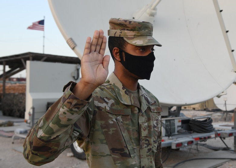 Senior Airman Aron Franks, assigned to the 16th Expeditionary Space Control flight deployed Al Udeid Air Base, Qatar, raises his right hand as he enlists into the U.S. Space Force on Sept. 1, 2020. The Space Force is the United States' newest service in more than 70 years. (U.S. Air Force photo by Staff Sgt. Kayla White)