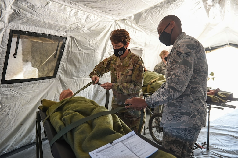 Gen. Jacqueline Van Ovost, Air Mobility Command commander, learns how to secure a patient to a litter from Senior Airman Dominique Springswoodley, 446th Aeromedical Staging Squadron medical technician, during her base tour at Joint Base Lewis-McChord, Wash., Sept. 3, 2020. The objective of the AMC leadership's visit is to learn from and listen to AMC Airmen and their families. (U.S. Air Force photo by Airman 1st Class Mikayla Heineck)