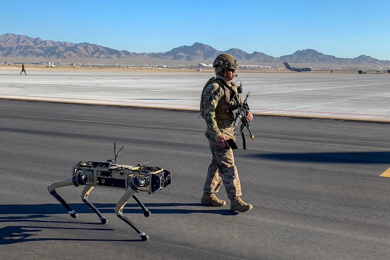 U.S. Air Force Tech. Sgt. Johnny Rodriguez, 321st Contingency Response Squadron force protection craftsman and lead defender for the CR team, walks with the robot dog during an agile combat employment exercise Sept. 3, 2020, at Nellis Air Force Base, Nevada. The robot dog is an experimental technology with the intent of aiding defenders to secure an airfield and is part of the Advance Battle Management System, which is being tested during ACE exercise. (Courtesy Photo)