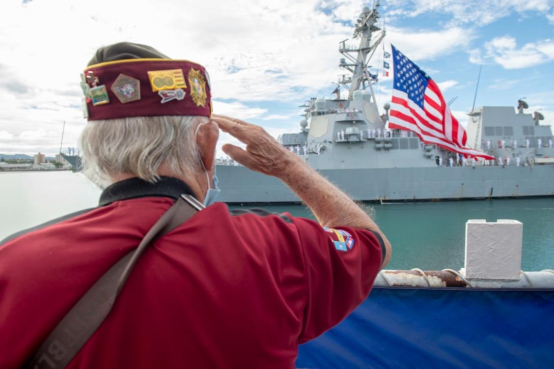 A veteran salutes a military ship.