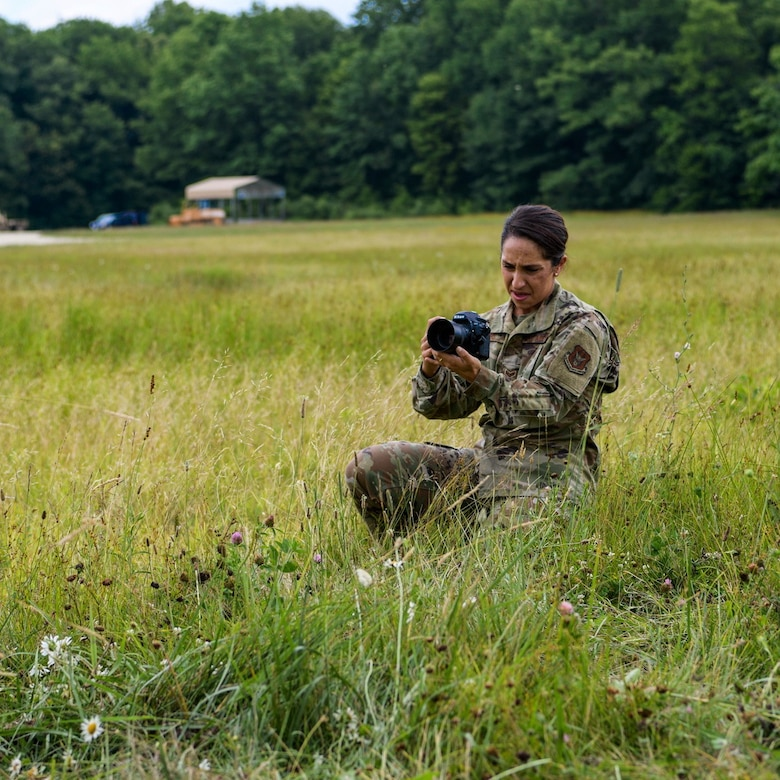 Senior Airman Christina Russo, a public affairs specialist with the 910th Airlift Wing, takes a video of a cargo drop training mission, July 14, 2020, at Camp Garfield in Ravenna, Ohio. As a public affairs specialist, Russo is trained to capture both still photography and video to tell the Air Force story.