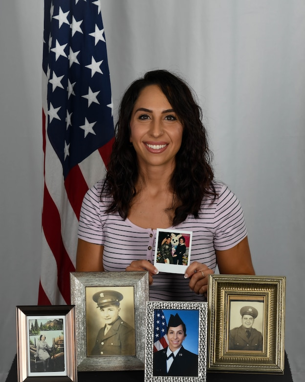 Senior Airman Christina Russo, a public affairs specialist with the 910th Airlift Wing, poses for a photo on Aug. 13, 2020, at Youngstown Air Reserve Station. The photos on display represent the military lineage within her family.