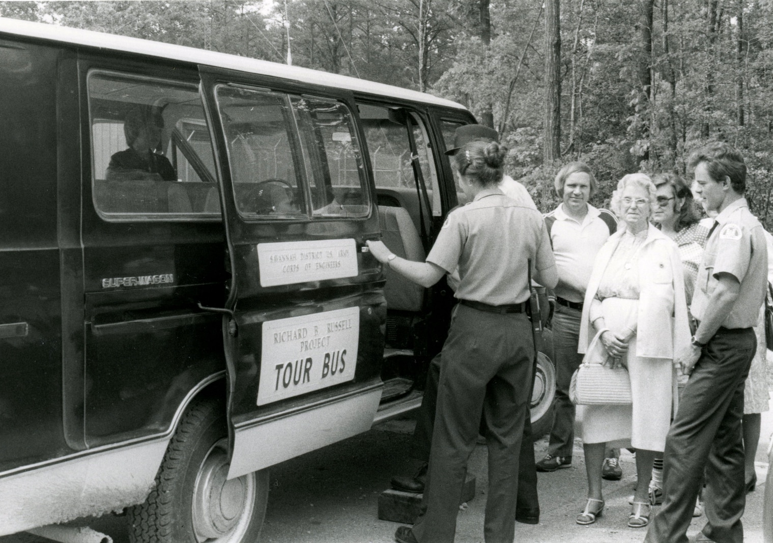 Two park rangers assist s small group of visitors into a van marked with a Tour Bus decal