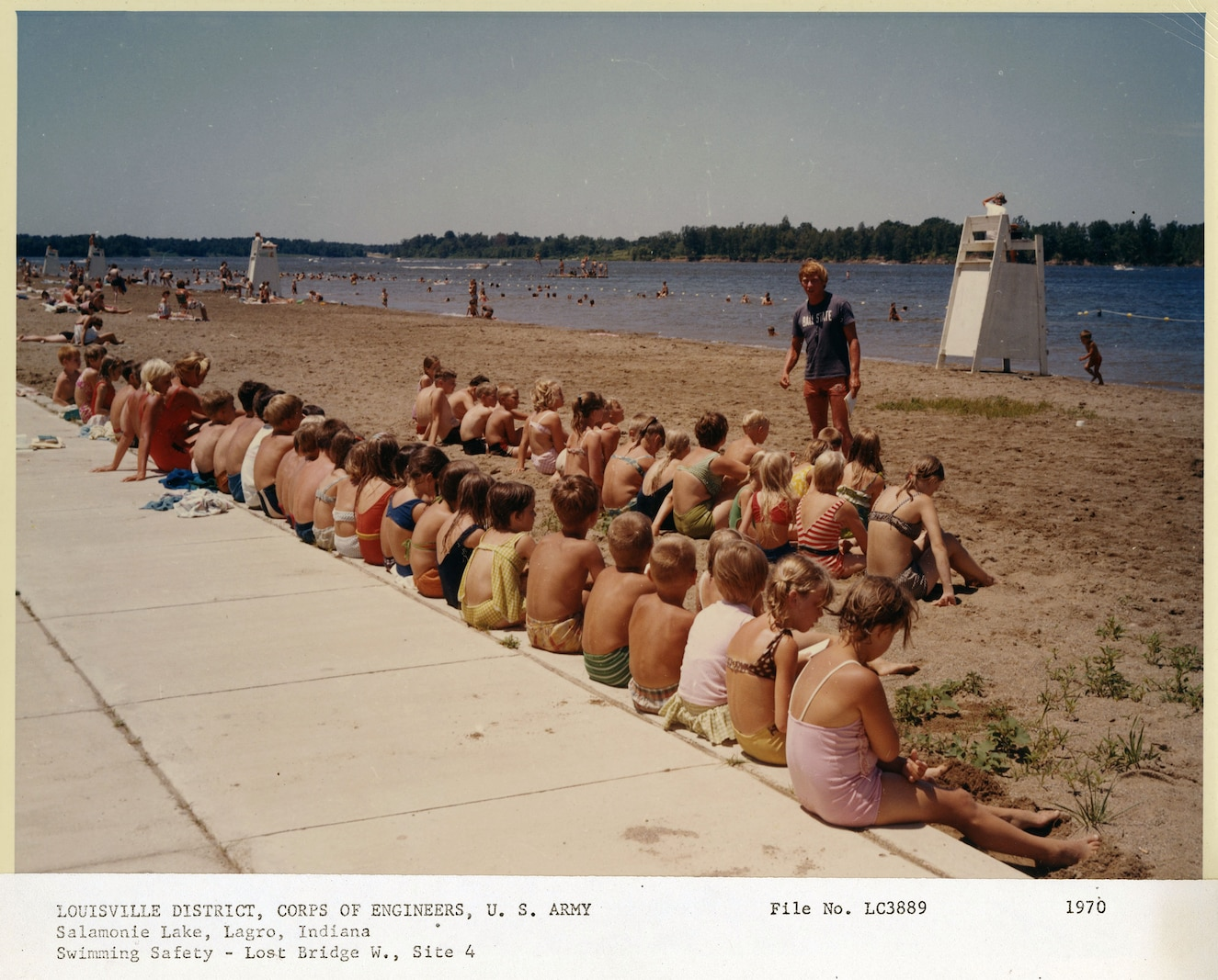 Children sit in rows on the sand listening to a male lifeguard give a swimming safety lesson with lake in the background