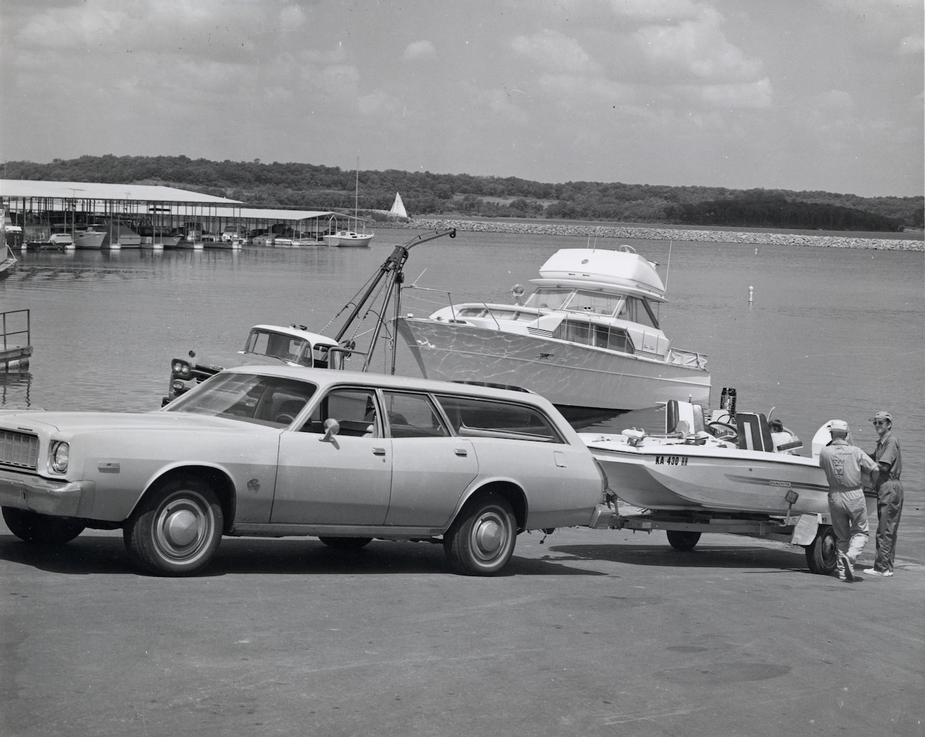 A station wagon backs a small boat down a ramp to the shoreline as two men watch