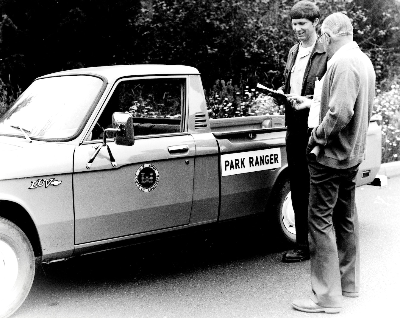 A park ranger and a visitor stand outside a small pickup truck with the Corps logo and park ranger decals