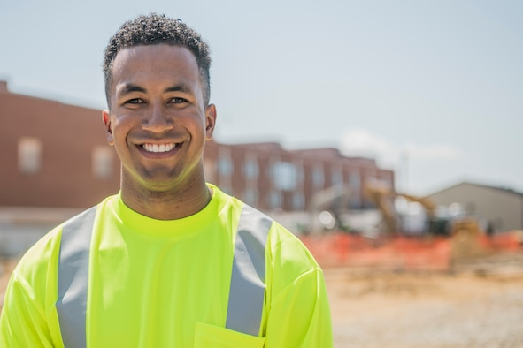 A man wearing a bright colored construction vest smiles for a photo