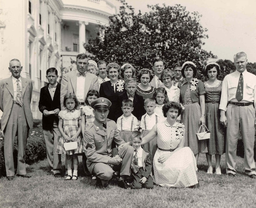 A large family poses on a lawn together.