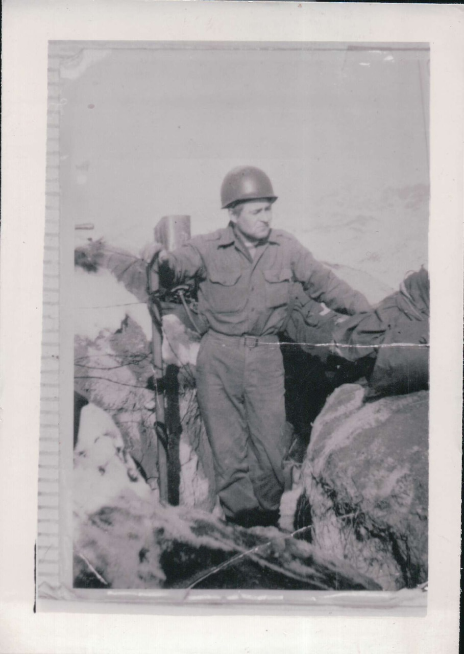 A helmet-clad soldier stands by a bunker with his hand on a metal pole.