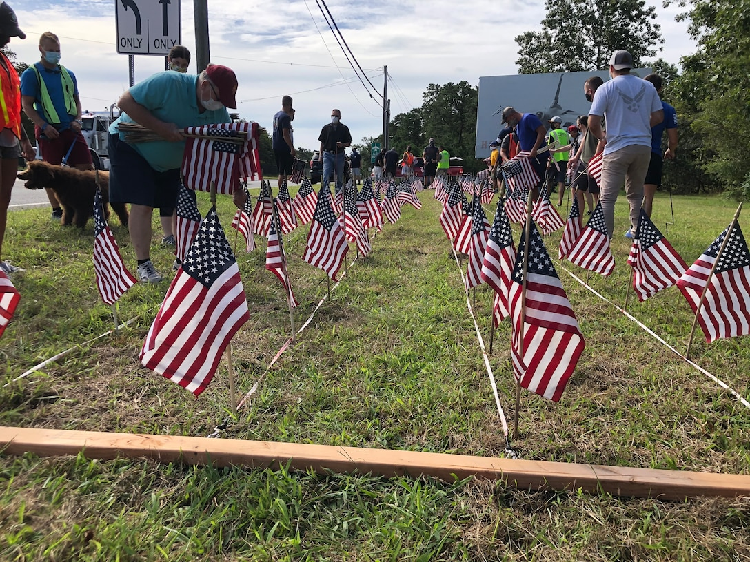 A photo of U.S. military veterans with the Flags for the Forgotten Soldiers organization, members of the Egg Harbor Township police department and members of the 177th Fighter Wing placing American flags in the ground.