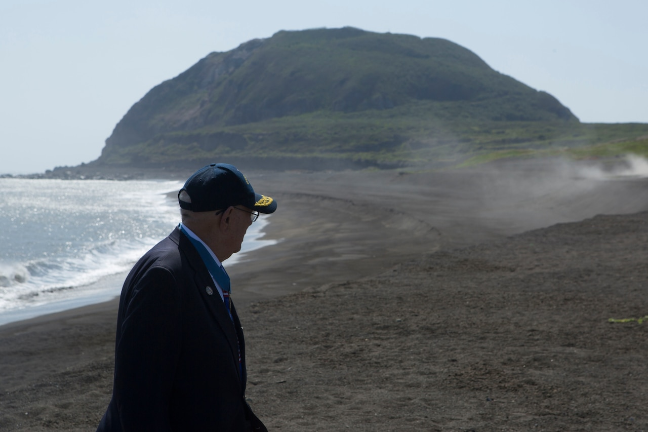 A man gazes at a hill. A shoreline is in the background.