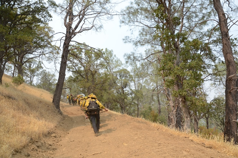 Joint Task Force Rattlesnake team members climb the steep slope of Rumsey Canyon to aid California Department of Forestry and Fire Protection (CAL FIRE) efforts to contain the LNU Lightning Complex fire near Rumsey, California, Aug 30, 2020. The task force is comprised of Soldiers and Airmen from the California National and State Guards and are trained by CAL FIRE as type II hand crews.