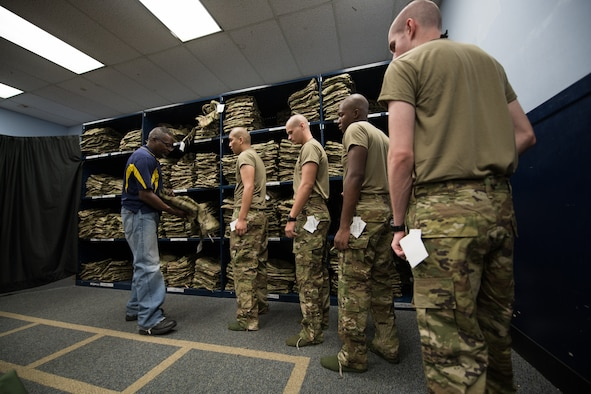 Airmen stand in line to get a uniform.
