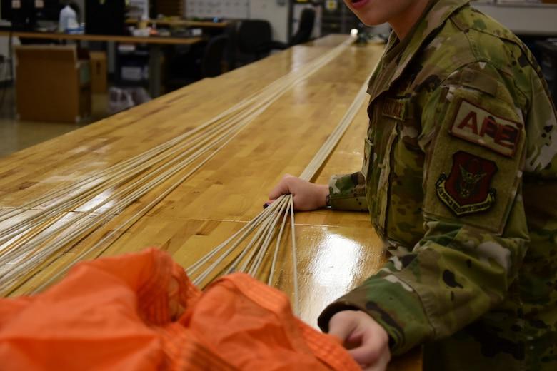 A photo of an Airman inspecting a parachute