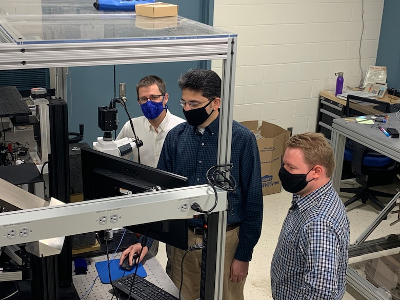 From left to right: Dr. Derek Bas, Dr. Piyush Shah and Dr. Michael Page examine a potential acoustically driven ferromagnetic resonance material under a microscope in the magneto-optics lab. The microscope is designed to observe magnetic properties on a small scale. (U.S. Air Force photo/Michael Wolf)