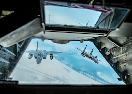Two U.S. F-15Cs from Prince Sultan Air Base, Kingdom of Saudi Arabia fly behind a KC-10 Extender assigned to the 908th Expeditionary Air Refueling Squadron, 380th Air Expeditionary Wing during a large force employment, Aug 25, 2020, at Al Dhafra Air Base, United Arab Emirates.