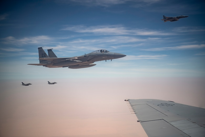 Two U.S. F-15C Eagles from 44th Expeditionary Fighter Squadron, Prince Sultan Air Base, Kingdom of Saudi Arabia (foreground) and two French Rafales fly along a KC-10 Extender assigned to the 908th Expeditionary Air Refueling Squadron, 380th Air Expeditionary Wing during a large force employment at Al Dhafra Air Base, United Arab Emirates Aug. 25, 2020.