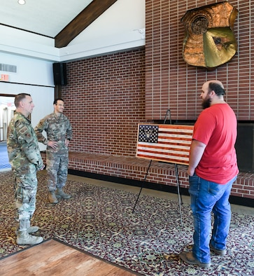 Brandon Champion, right, an Arnold Engineering Development Complex (AEDC) instrumentation technician, speaks with AEDC Commander Col. Jeffrey Geraghty, center, and AEDC Superintendent Chief Master Sgt. Robert Heckman about the artistic representation of a flag he made and gifted to the Air Force, Aug. 7, 2020, at Arnold Lakeside Center at Arnold Air Force Base, Tenn. Champion gifted the flag in recognition of the AEDC response to the COVID-19 pandemic. (U.S. Air Force photo by Jill Pickett)