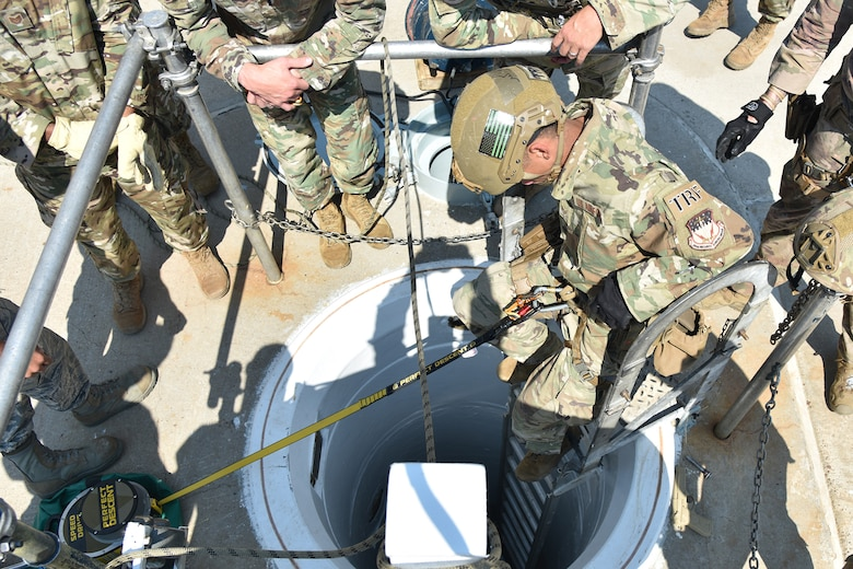 An Airman is at the top of a ladder, descending into a shaftway into a launch facility.