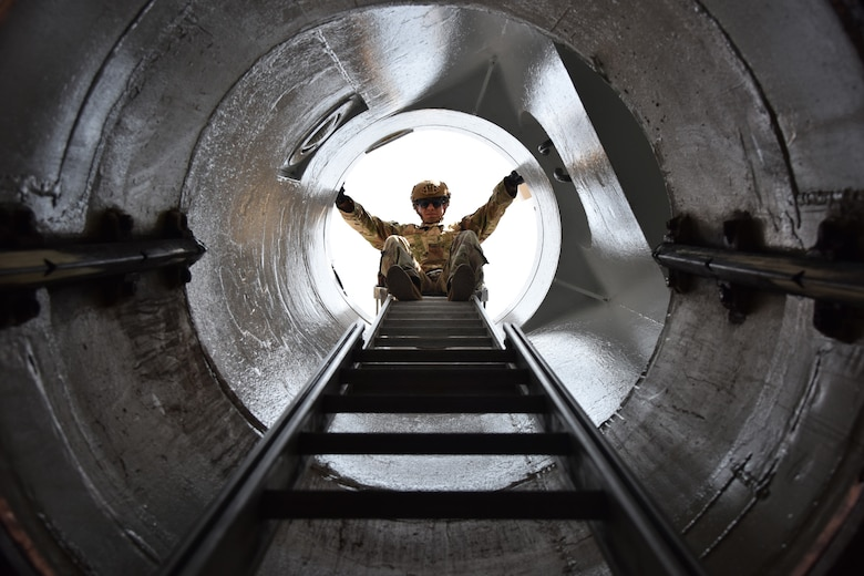 An Airman stands on a ladder and looks down a shaftway into a launch facility.