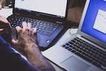 Cropped photo of two laptops and a person typing on one of them. (Photo by Unsplash.com)