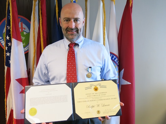 DLA Liaison Officer (male) poses with an Army Civilian Service Commendation certificate.
