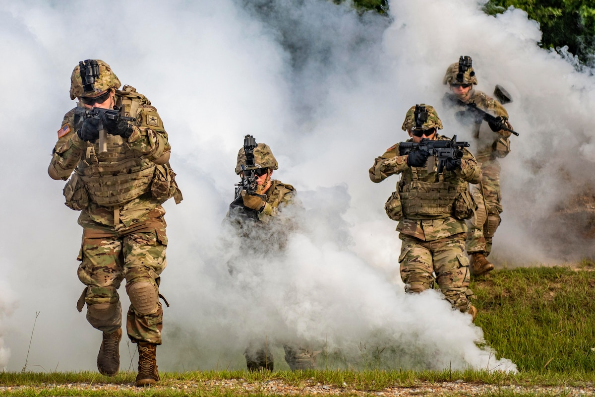 Four soldiers hold weapons as smokes surrounds them.