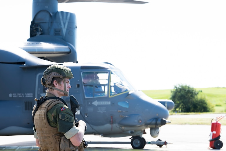 A Norwegian military member stands guard in front of a CV-22B Osprey, based out of RAF Milden-hall, U.K., during a training mission at Rygge Air Station, Norway, August 25, 2020. Integration with the Norwegian Air Force allowed the 352d Special Operations Wing to enhance and strengthen bonds with our partner nation and further secure the strategic high-north region. The exercise provided train-ing for 352d Special Operations Wing members on capabilities such as personnel recovery, forward area refueling point, aerial refueling, maritime craft delivery system, and fast rope training. (U.S. Air Force photo by Staff Sgt. Michael Washburn)