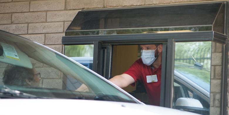 Mason Bushey, 56th Medical Group pharmacy technician, provides prescriptions through a drive-thru window Aug. 24, 2020, at Luke Air Force Base, Ariz.