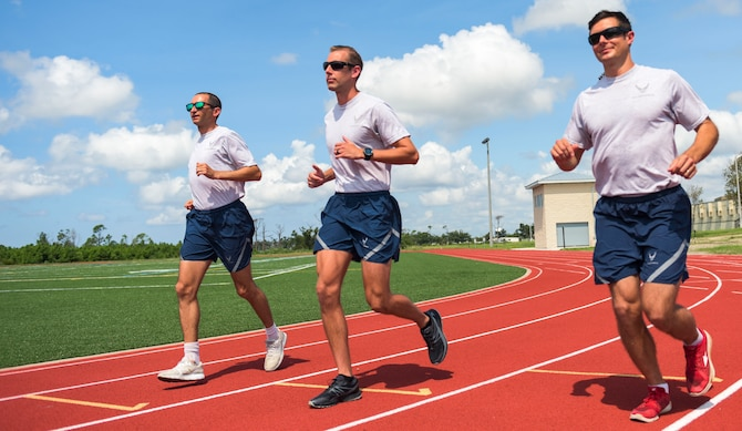 U.S. Air Force Capt. Robert Friedman with the Air Force Legal Operations Agency, left, Tech. Sgt. Joshua Skinner with the 601st Air Operations Center, and Capt. Kyle Imhoff with the Air Force Civil Engineer Center, right, run on the fitness track at Tyndall Air Force Base, Florida, Sept. 8, 2020. The Tyndall Focus 5/6 group organized a running event where runners tracked miles during the month of August. The top three runners were recognized and included Skinner with 348 miles, Friedman with 356 miles, and Imhoff with 366 miles. (U.S. Air Force photo by Staff Sgt. Magen M. Reeves)