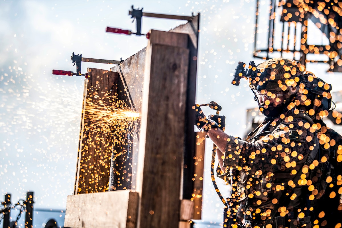 Sparks fly around a Marine using a welding tool on a ship's deck.