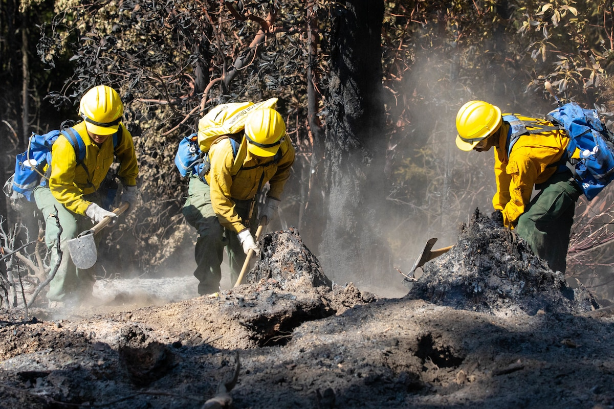 Three soldiers in firefighting gear dig in the dirt.