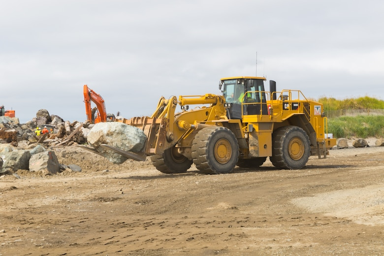 """A construction crewmember moves a stone so excavators can place it on the South Jetty near Hammond, Ore., Aug. 31. The Portland District, U.S. Army Corps of Engineers has been rehabbing the jetty system for the last several years (completing work on Jetty """"A"""" in 2018 and North Jetty in 2019) and just started work on South Jetty in June. On Aug. 31, the Corps, the Pacific Northwest Waterways Association (PNWA), the U.S. Coast Guard and several members of Congress gathered to commemorate that progress. (U.S. Army photo by Jeremy Bell)"""