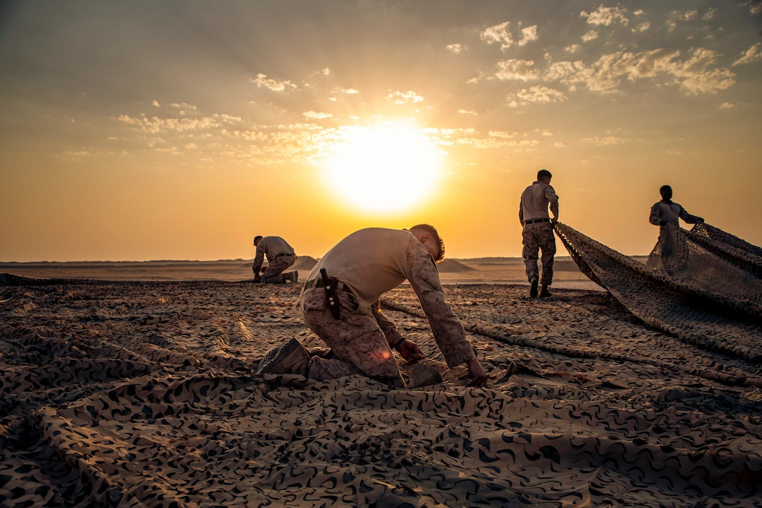 Marines work on a large canopy laid out flat on the ground on desert terrain, with a low sun and orange sky in the background.