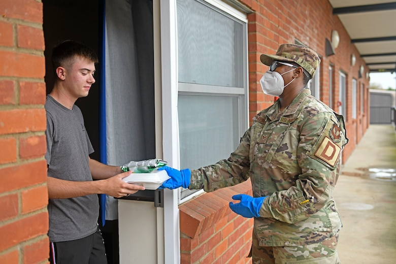 U.S. Air Force Senior Airman Nnkeha Streeter, 100th Maintenance Squadron aerospace ground equipment journeyman and Quarantine and Isolated Team member, delivers a meal to an Airman in quarantine at Royal Air Force Mildenhall, England, Sept. 3, 2020. The Qni Team preserves, supplies and supports the social, mental, physical and spiritual needs of Airmen and their families when quarantined. (U.S. Air Force photo by Staff Sgt. Mackenzie Mendez)
