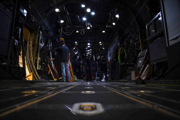 Men working on the inside of a large military aircraft