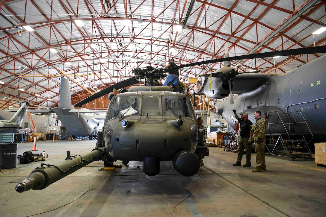 Men standing around a military helicopter that is in maintenance