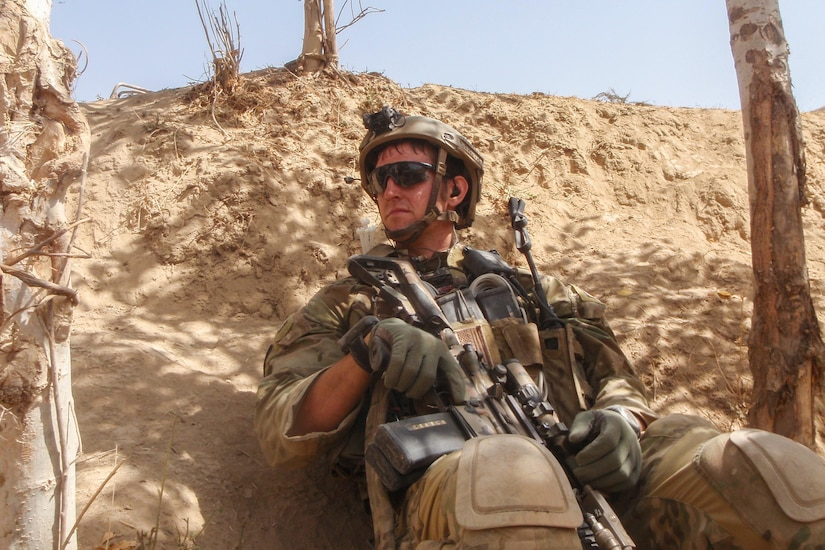 A soldier holding a weapon sits in a desert like area.