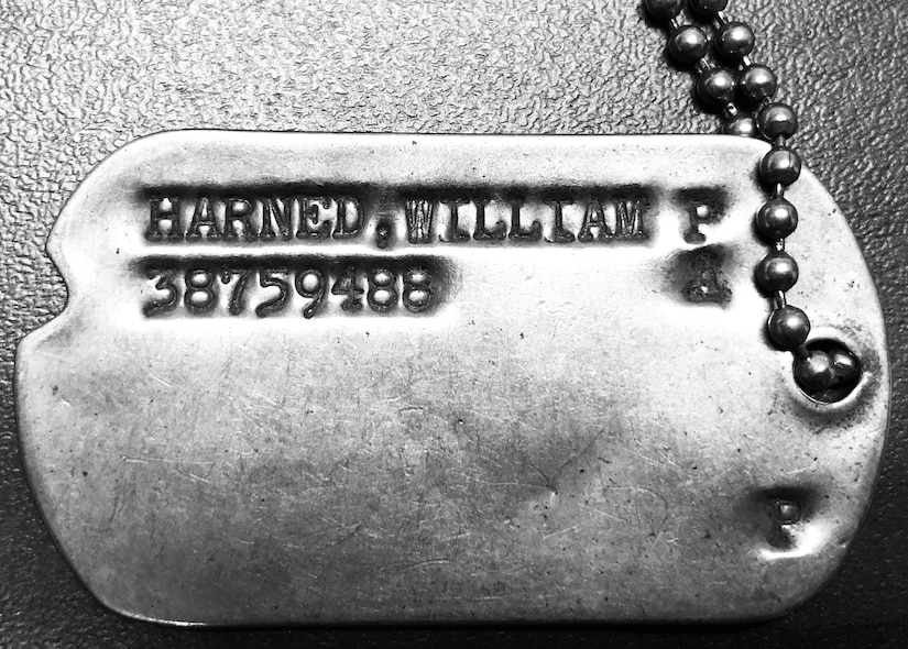 "A military dog tag is stamped ""Harned, William P. 38759488."""