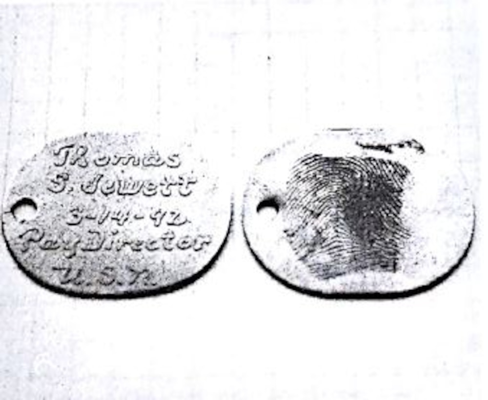 Two dog tags are displayed; one shows writing while the other shows a fingerprint.