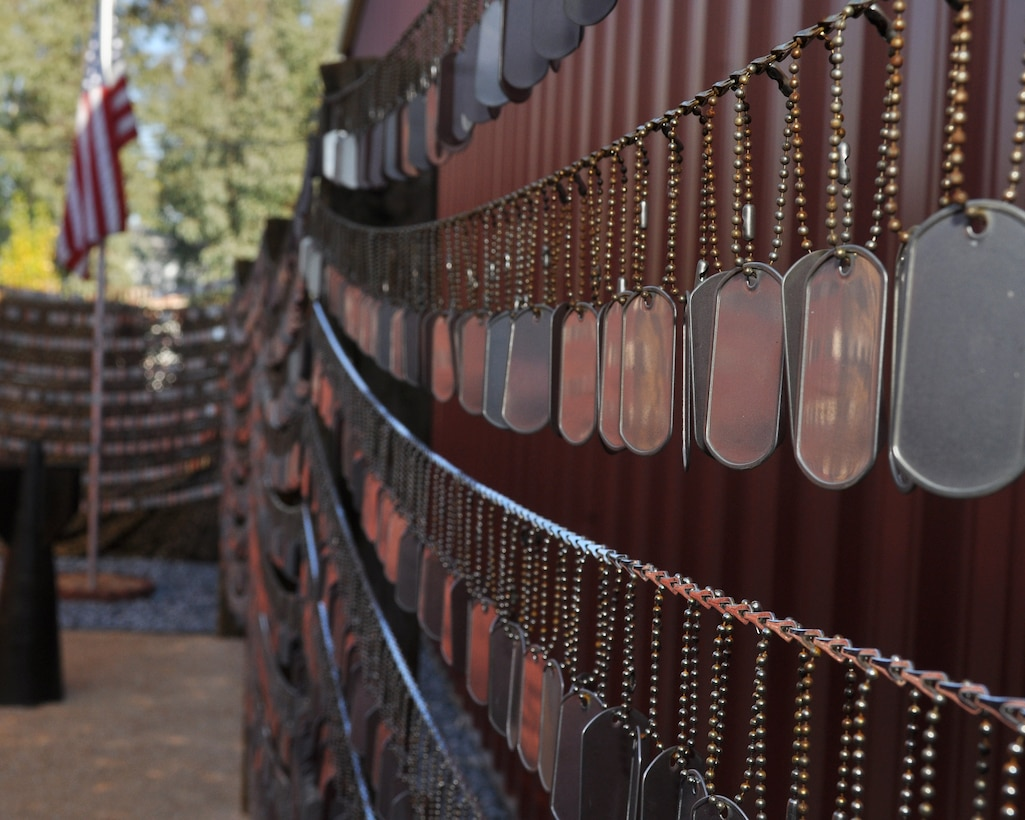 Rows of dog tags hang from chains on a wall. An American flag sits in the background.