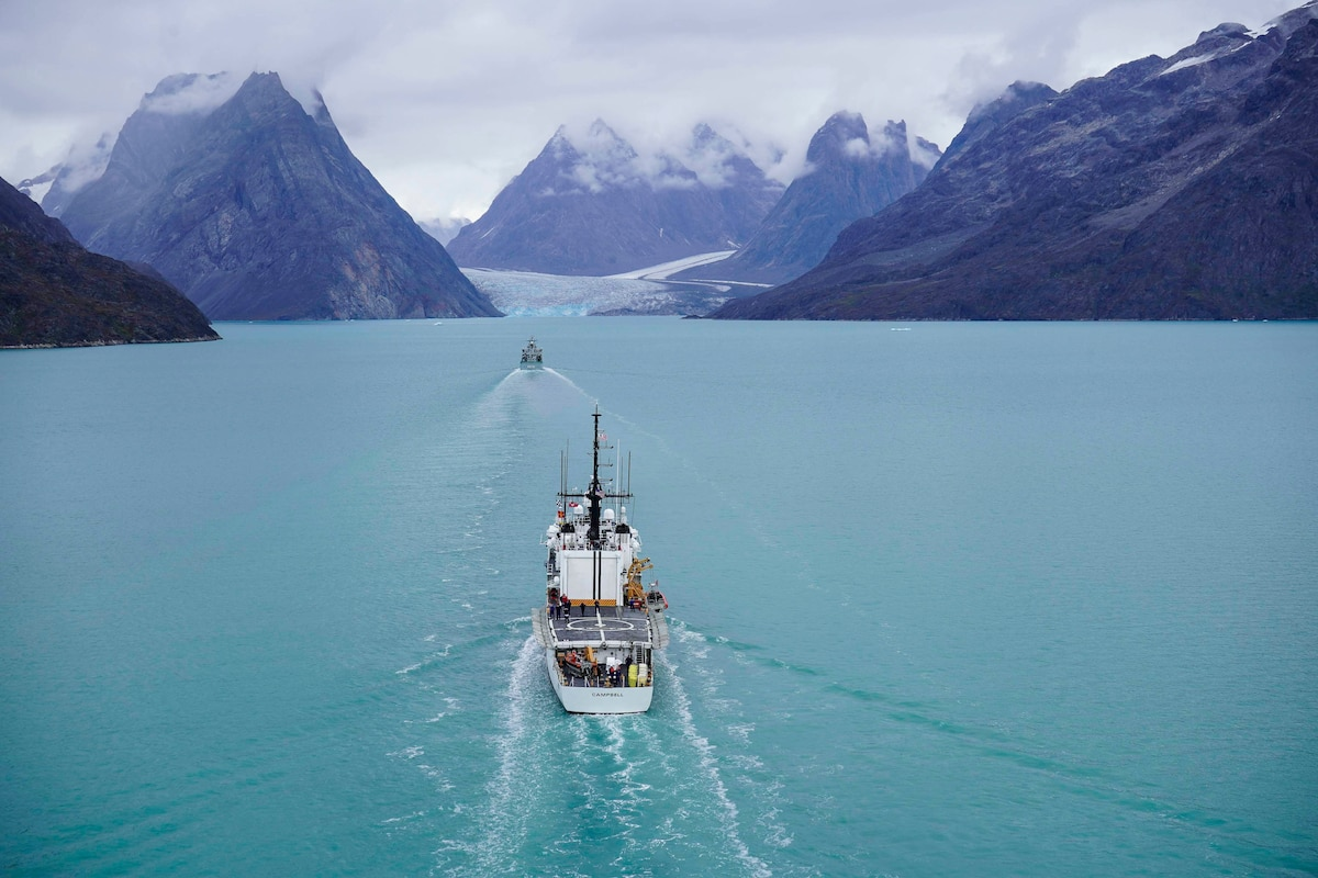A Coast Guard cutter travels in waters surrounded by mountain peaks.