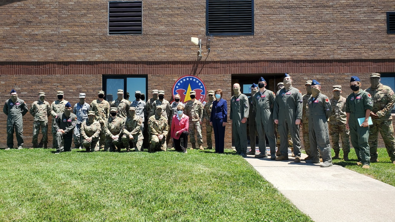 28 Military members, in uniform, pose for a group photo with the Secretary of the Air Force, Barbara Barrett, outside on the grass next to the squadron building.