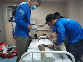 Medical professionals evaluate an injured Chinese sailor Aug. 27, 2020.