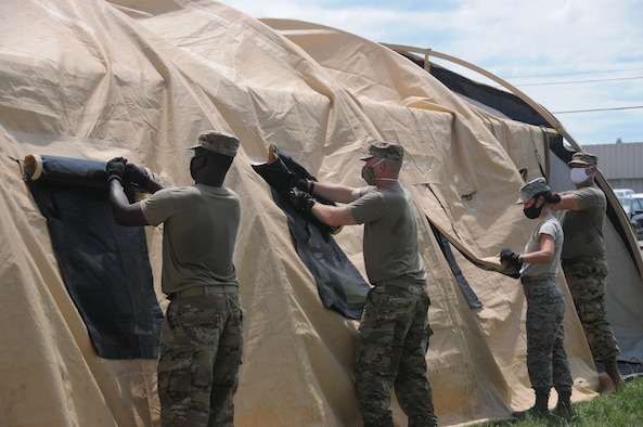 Airmen from the 445th Aeromedical Staging Squadron work together during a training event to build a tent that will act as a staging ground for patients before they are transported out to the flightlline and flown to a hospital.