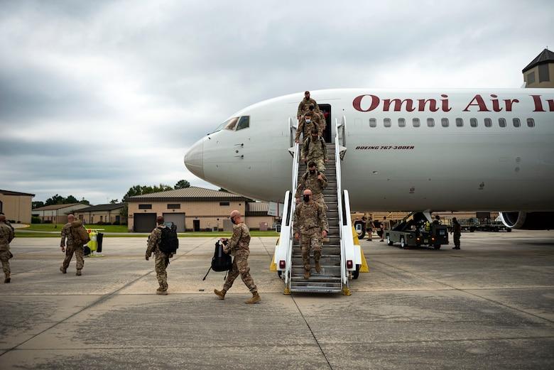 Photo of Airmen exiting an aircraft.