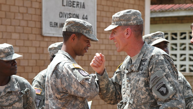 Joint Forces Command–United Assistance commander Major General Gary Volesky, right, elbow bumps Sergeant 1st Class Roderick Davis, logistics section noncommissioned officer in charge, 129th Combat Sustainment Support Battalion, 101st Sustainment Brigade, Task Force Lifeliner, during visit to Monrovia, Liberia, November 6, 2014 (U.S. Army/Mary Rose Mittlesteadt)