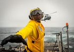 """Sailor directs MH-60 Sea Hawk helicopter assigned to """"Warlords"""" of Helicopter Maritime Strike Squadron 51 as it takes off on flight deck aboard USS McCampbell during vertical replenishment training, East China Sea, March 27, 2020 (U.S. Navy/Markus Castaneda)"""